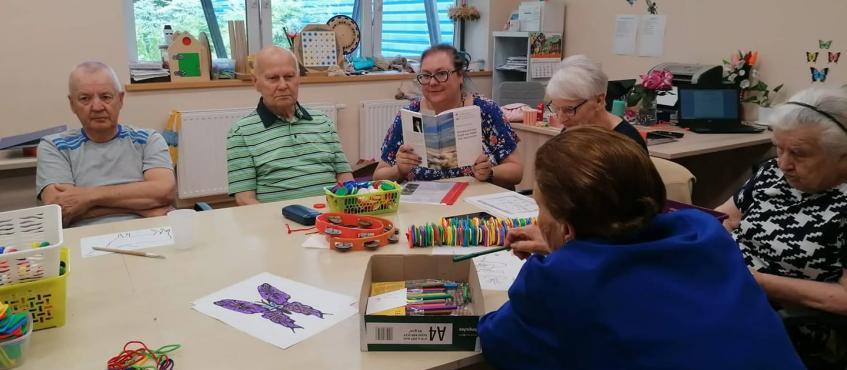 Pięć osób słucha bajki czytanej przez opiekuna. Siedzą przy stole