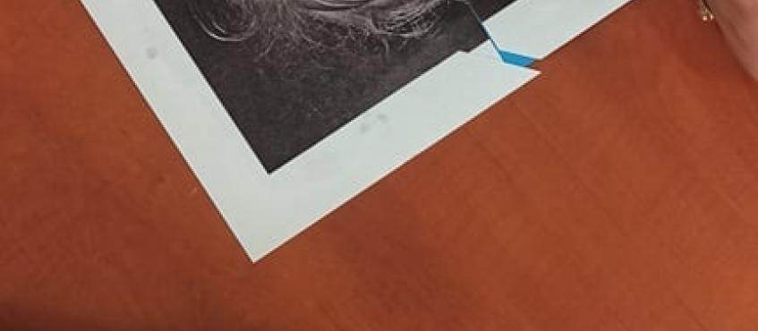 zdjęcie przedstawia wyklejany obraz oraz ręce osób, które składają obraz w całość