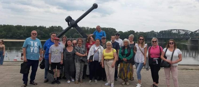 duża grupa osób stoi na tle wielkiej kotwicy. za grupą płynie rzeka