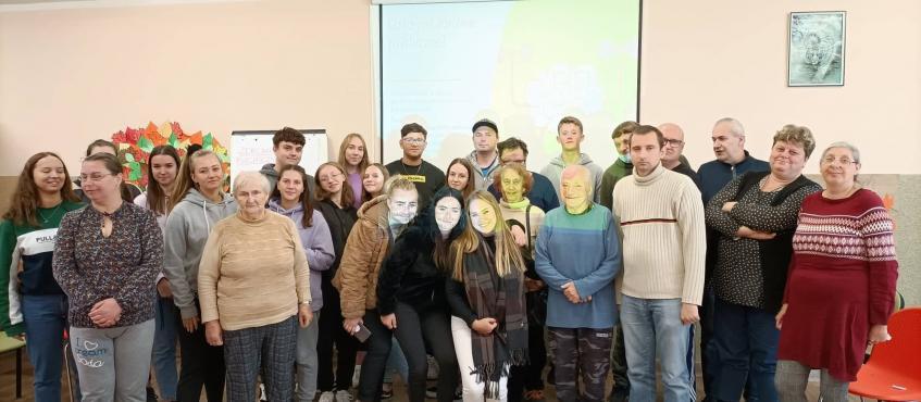 Przed ekranem do zdjęcia pozuje duża grupa osób w różnym wieku